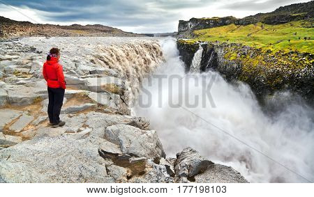 Panoramic view of woman standing near famous Dettifoss waterfall in Vatnajokull National Park Northeast Iceland