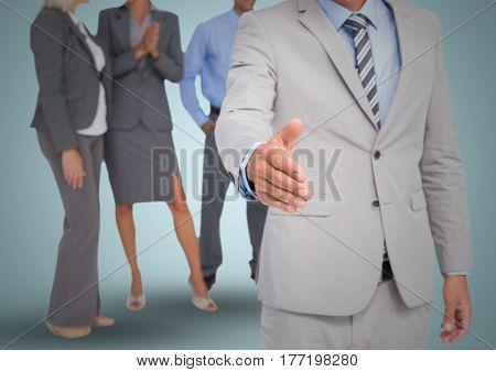 Digital composite of Handshake in front of business people against blue backgrund