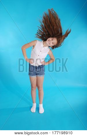 Young girl throws up her hair isolated on blue
