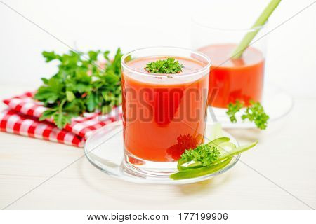 Tomato Juice In Transparent Glasses With Parsley, Cucumber And Napkin On Light Wooden Background, Cl