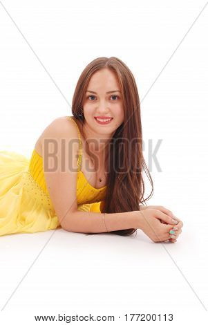 Beautiful woman with brown hair in elegant yellow dress lying on white background