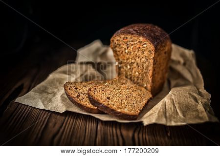 Sliced Brown Bread On Paper Over Wooden Background, Rural Style, Close Up