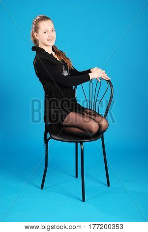 Cheerful young girl are sitting on a chair against the blue background