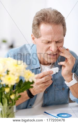 Take it away. Frustrated male wearing jeans shirt, wrinkling his forehead while holding napkin