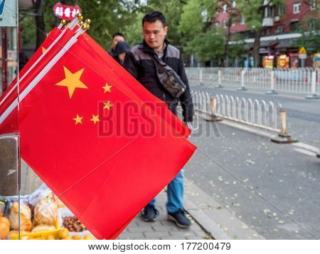 Beijing, China - Oct 30, 2016: Flags of the People's Republic of China by a store's door while pedestrians walk by. Image captured along a street in Old Beijing.