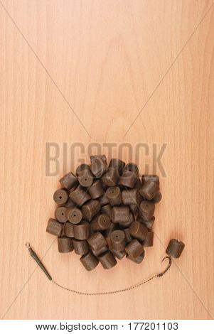 Fishing bait with hook and brown pre-drilled halibut pellets for carp fishing isolated on wood background with soft shadow