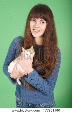 Beautiful smiling brunette girl and her cat over green background