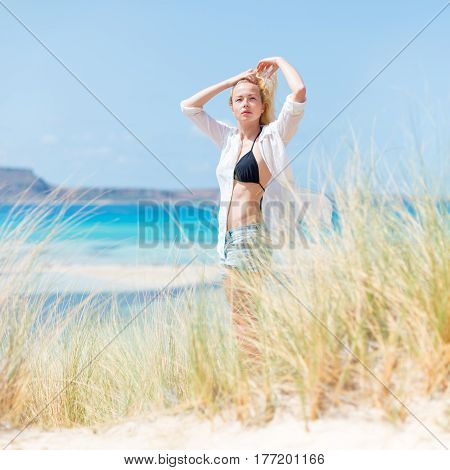 Relaxed woman wearing unpinned white shirt and black bikin, enjoying sun, freedom and life an a beautiful beach. Young lady feeling free, relaxed and happy. Concept of health well being.