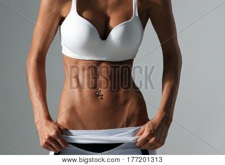 fitness and diet concept - close up of beautiful athletic female abs in sportswear on gray background