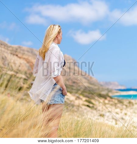 Relaxed woman in white shirt looking at distance, enjoying beautiful nature, freedom and life at serene landscape at Balos beach, Greece. Concept of vacations, freedom, happiness, joy and well being.