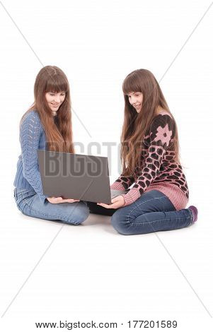 Portrait of two twins sisters with laptop on white background