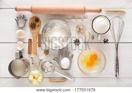 Baking background. Cooking ingredients and utencils for yeast dough and pastry on white rustic wood. Top view, flat lay