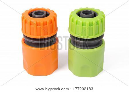 Orange and green garden water hose nozzle and connectors isolated on white background with soft shadow