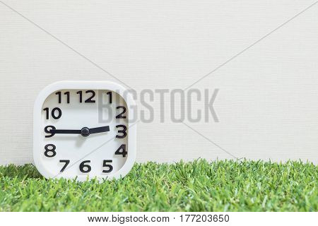Closeup white clock for decorate show a quarter to three o'clock or 2:45 a.m. on green artificial grass floor and cream wallpaper textured background with copy space