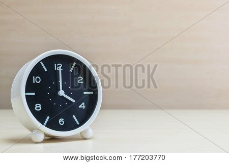 Closeup alarm clock for decorate in 4 o'clock on brown wood desk and wall textured background with copy space