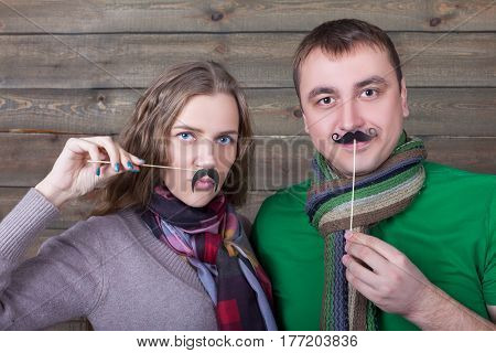 Cute couple with funny moustache on a sticks
