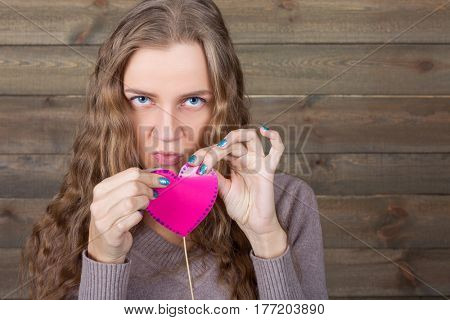 Young female with funny pink heart on a stick