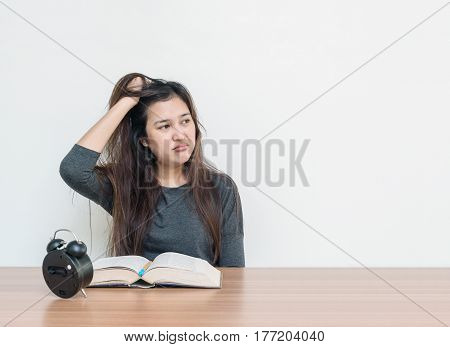 Closeup asian woman sitting for read a book with strain face emotion on wood table and white cement wall textured background with copy space