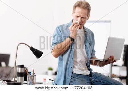 Just work. Confident male sitting on his table, wiping his nose while looking downwards