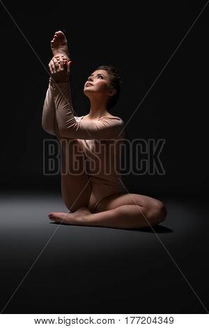 Pretty woman in beige body sitting on the floor and streching her leg up in a dark studio