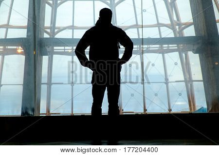 Silhouette of man standing back over big window