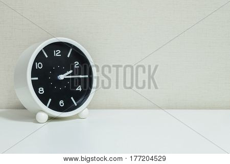 Closeup black and white alarm clock for decorate show a quarter past two o'clock or 2:15 p.m.on white wood desk and cream wallpaper textured background with copy space