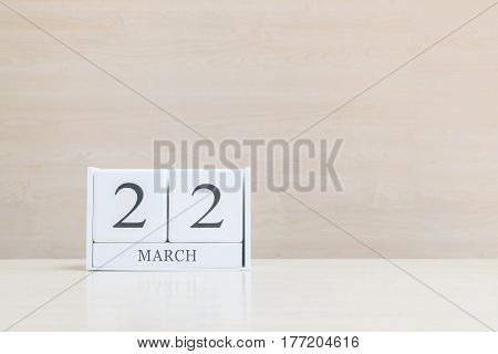 Closeup surface white wooden calendar with black 22 march word on blurred brown wood desk and wood wall textured background with copy space selective focus at the calendar