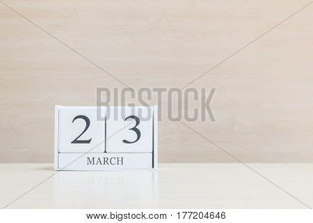 Closeup surface white wooden calendar with black 23 march word on blurred brown wood desk and wood wall textured background with copy space selective focus at the calendar