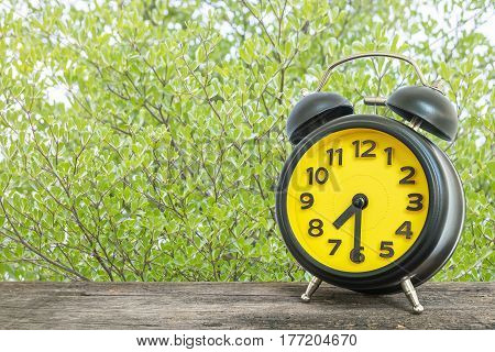 Closeup black and yellow alarm clock for decorate show half past seven or 7:30 a.m. on old brown wood desk on green leaves in the park textured background