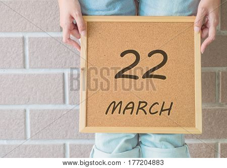 Closeup calendar at the cork board in hand of asian woman in front of her legs with 22 march word on brick wall textured background