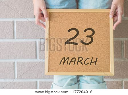 Closeup calendar at the cork board in hand of asian woman in front of her legs with 23 march word on brick wall textured background
