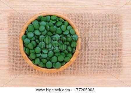 green pills spirulina and chlorella seaweed close up n the wooden bowl top view