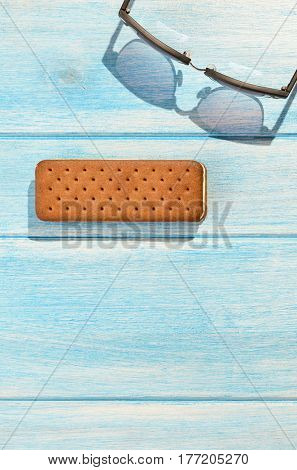 Ice cream sandwich with retro sunglasses on blue table outdoors