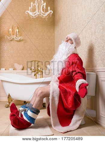 Santa Claus with pants down sitting on the toilet