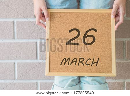 Closeup calendar at the cork board in hand of asian woman in front of her legs with 26 march word on brick wall textured background