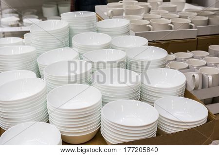 Empty white glass bowls in piles in supermarket