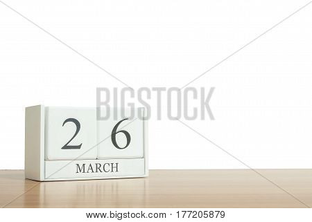 Closeup surface white wooden calendar with black 26 march word on blurred brown wood desk isolated on white background with copy space selective focus at the calendar