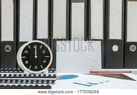 Closeup white clock for decorate in 12 o'clock desk of officer with work paper and document file in office room textured background in work concept