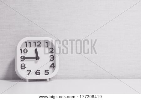 Closeup white clock for decorate show a quarter to twelve o'clock or 11:45 a.m. on white wood desk and cream wallpaper textured background in black and white tone with copy space