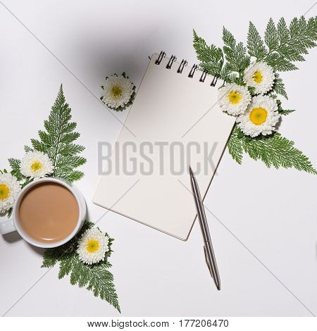 Flat lay of green leaves and flowers pattern with cup of coffee and paper note on white background