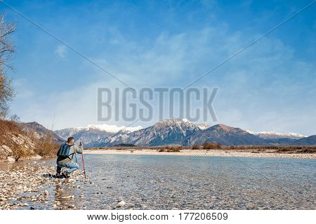 Mature hiker on the bank of a river. Trekking toward mountain. Rambler about 60 years old. Active retirement. Copy space