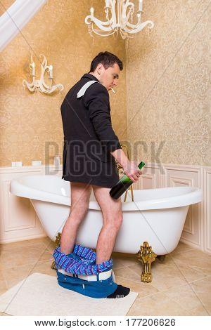 Funny drunk man peeing in luxury bath