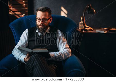 Bearded writer in glasses reads handwritten text