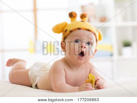 Baby boy in a funny giraffe hat lying on his belly in nursery. Little kid lies on bed with opened mouth and holds soother in his hands