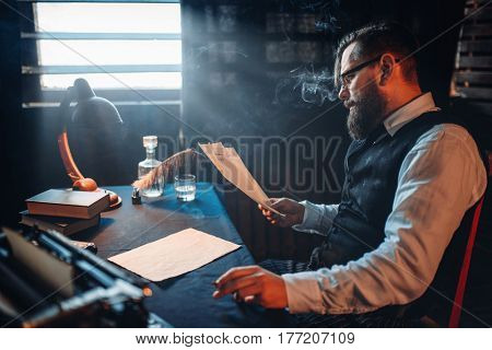 Bearded writer smokes and reads handwritten text