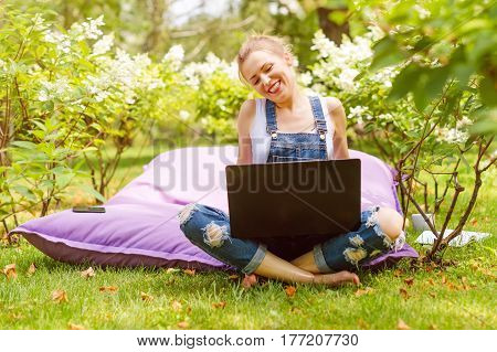 Happy freelancer working in the garden. Writing, surfing in the internet using laptop. Young woman relaxing and having fun in park area. Distance education, freelance concept