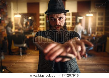 Barber in hat holding scissors and straight razor
