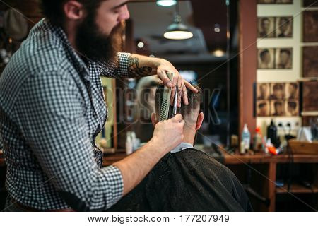 Bearded coiffeur cutting hairstyle by scissors