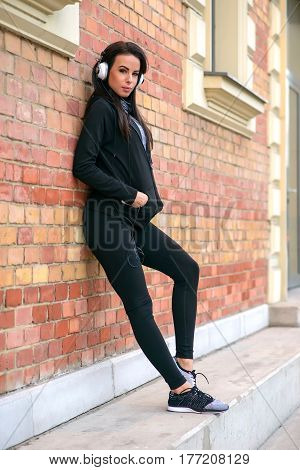A beautiful young woman wearing sportswear and leaning to a brick wall while listening music on her headphones