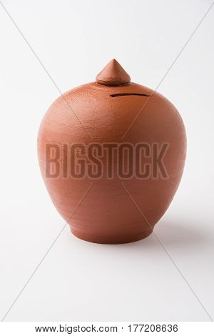 Typical terracotta money saving box or piggy bank isolated over white background